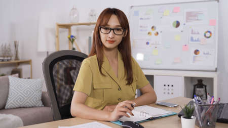 confident smiling asian japanese female secretary looking at camera and holding pen while sitting in personal modern office.