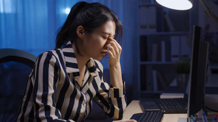 exhausted korean female employee working to a tight deadline while struggling with tired eyes in late night office.