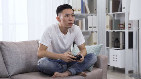 handsome asian man holding wireless controller is playing video game in concentration on sofa in bright living room at home Zdjęcie Seryjne