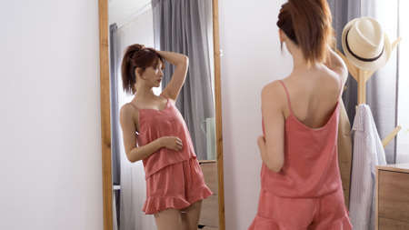 sexy young asian chinese lady in charming pajamas standing in front of mirror and holding hair up into a ponytail in the morning. Zdjęcie Seryjne
