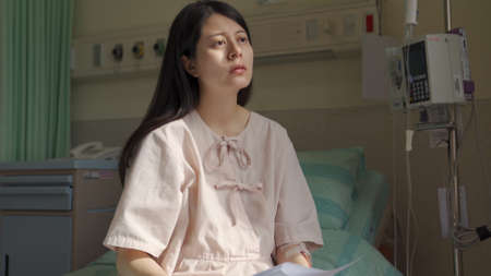 frowning illness japanese female patient looking into distance at a loss and feeling upset about getting serious health problem Zdjęcie Seryjne