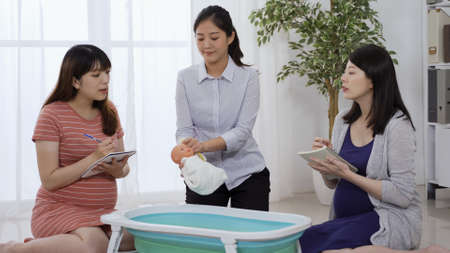 asian japanese expectant mom in blue dress taking parenting class with her friend and asking questions to nurse.