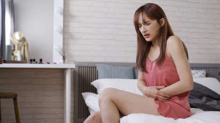 beautiful asian korean woman in sleepwears sitting at bedside and holding belly with painful look due to the bad stomach ache