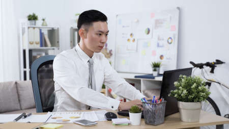 serious asian chinese male worker writing email on notebook is encountering difficulty while trying to negotiate with the firm.