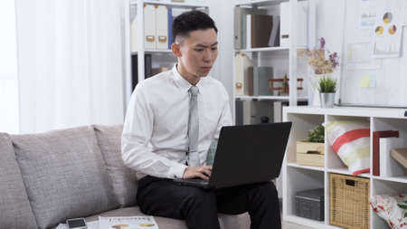 concentrated asian guy worker in suit seated on sofa is preparing financial statement with notebook and document.