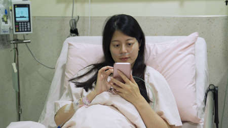 portrait of asian girl patient with feeble look but recovering well from coronavirus disease lying in bed and browsing online website on cellphone.