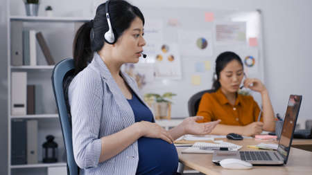 asian chinese pregnant online service agent wearing headsets is looking at laptop screen and explaining with hands gestures in bright office Zdjęcie Seryjne
