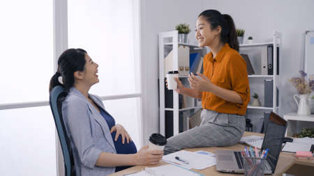 cheerful asian expectant woman laughing and chatting with her business partner while having hot coffee in paper cup in modern office.