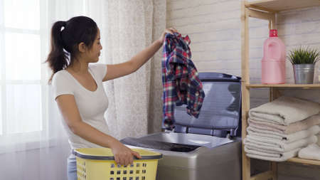 elegant asian chinese woman putting all the dirty clothes into washing machine from basket during daytime.