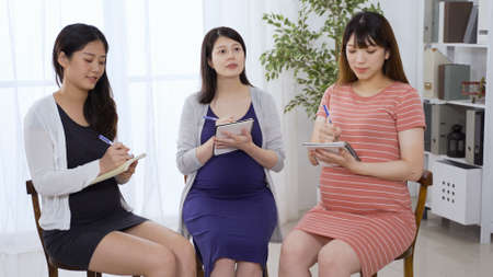 group of asian chinese pregnant ladies sitting together staring ahead and taking notes during antenatal class in bright meeting room. Zdjęcie Seryjne