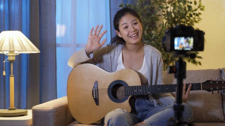 asian female live streamer waving hi to her audience and beginning to play the song on guitar while keep in social distancing during virus outbreak.