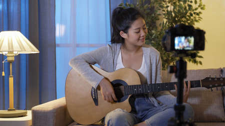 cheerful music influencer waving hands to greet her fans in front of digital camera and starting to play the guitar on sofa while shooting live performance video at home