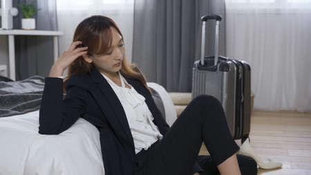 asian stressed businesswoman sitting by luggage, propping head in the bedroom, losing passion for work. depression, mental health concept