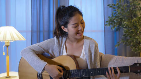 portrait of asian girl social media influencer playing music and recording guitar lesson at home in night