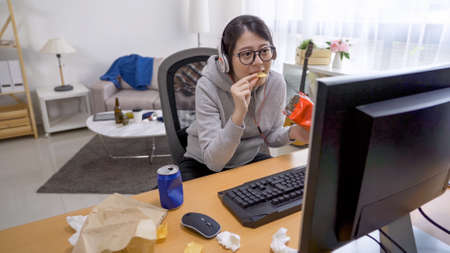 lazy young happy asian chinese girl filling her mouth with chips and concentrated looking on computer monitor at home