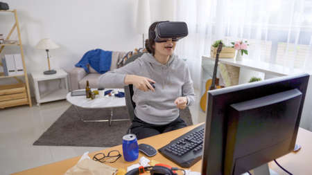 happy young girl homebody in vr headset having fun and cheerful laughing while playing game in messy bedroom.