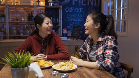happy charming asian japanese best sisters drinking bottles of beer and having fun in modern dark bar.