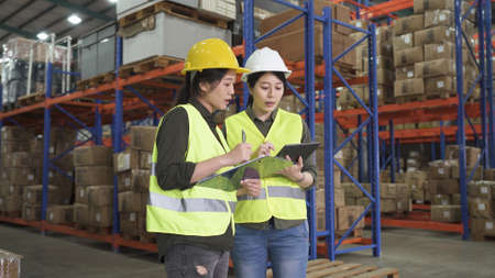 Two asian lady employees holding digital tablet computer and talking on placement plan in logistics center warehouse