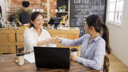 Smiling asian woman shaking hands to mortgage insurance broker at cafe meeting. happy lady handshaking with sales consultant making deal. male waiter prepare meal of customer order in counter.