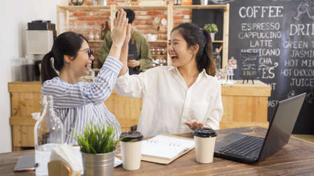 Happy pretty businesswomen giving high five in modern cafe store. two young girl coworkers deal with problem of annoyed customer using laptop excited celebrating. male coffeehouse staff in counter.