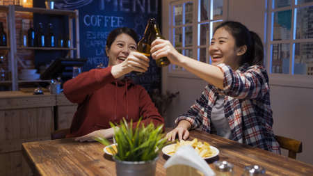 two young smiling asian korean women friends clinking bottles while celebrating success in night pub. Stock fotó