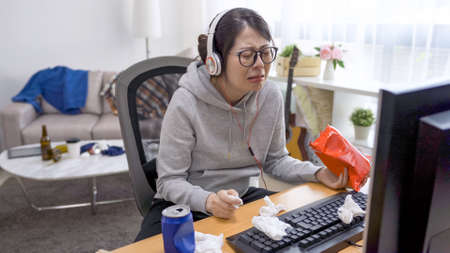 crying female homebody enjoy pack of chips and can beverage while watching movie on computer at home in messy bedroom.