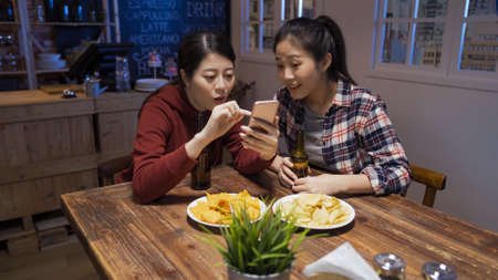 Two beautiful asian japanese women friends feeling curious while reading good news on mobile phone in night pub. Stock fotó