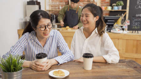 Two asian female coworkers talking at coffee shop while waiting for meal. girls colleagues friends chatting and laughing enjoy lunch break time together in cafe. man waiter prepare customer order