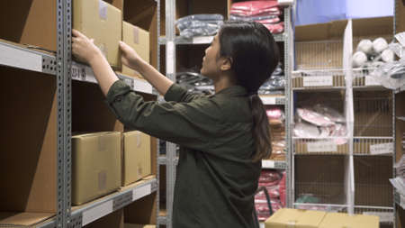 side view of warehouse asian korean lady worker puts cardboard box on shelf after searching empty place in storehouse.