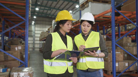 two asian female worker colleagues holding clipboard and digital pad and discussing new project in large stockroom Zdjęcie Seryjne