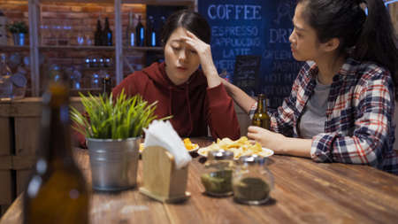 elegant asian japanese woman comforting and helping depressed friend to solve problem in bar at night.