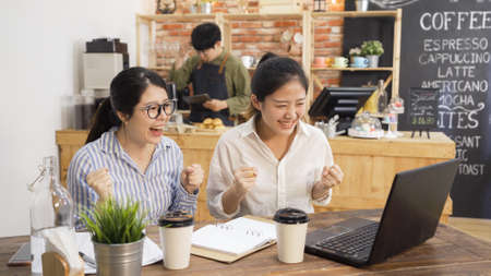 happy college student girls celebrate successful teamwork results in cafe bar. excited two asian woman working on project and pass exam in coffee shop. startup in coffeehouse male owner in counter Stock fotó