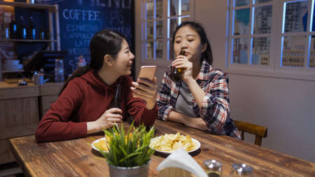 Cheerful old female friends communicate with each other and watching on mobile phone while drinking bottles of beer in night pub. Stock fotó