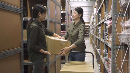 excellent teamwork of two warehouse asian chinese female staff colleagues passing cardboard box in large depot of factory.