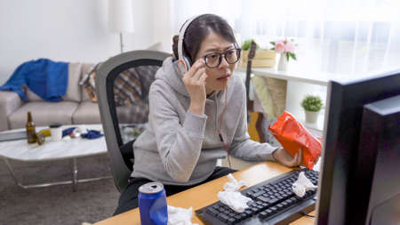 upset asian chinese lady in headphones eating snack and wiping tears by tissue while watching romantic movie online at home Stock fotó