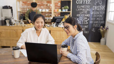two young girl colleagues sitting at wooden table in cafe bar working together on laptop computer. coworkers women discussing project meeting in coffee shop. male bartender in counter background Stock fotó