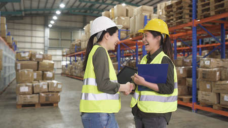 two laughing female storehouse operators in hard hat and safety vest shaking hand in large depot in company.