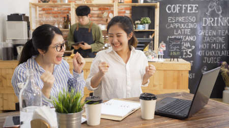 Group of excited colleagues women using laptop in cafe. two happy partners girls freelance with successful startup business concept. man waiter in apron standing in counter holding tablet working.