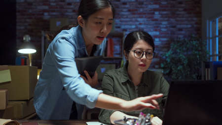 two chinese lady colleagues working together on laptop computer and discussing ways to solve problem on internet in dark office at night