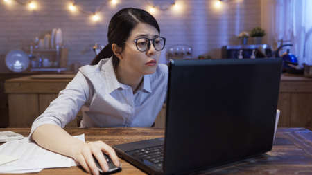 exhausted office lady staring at screen while sitting at desk and connecting to internet on laptop computer in evening.