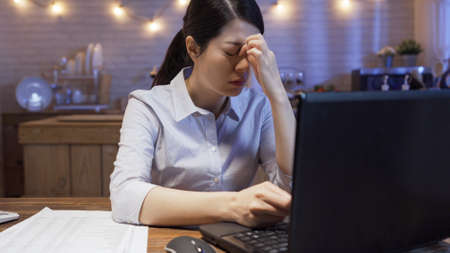 Tired young asian business woman feeling stressed because of deadline project problems while working on laptop computer in kitchen late at night.