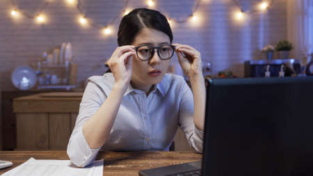 elegant frowning asian chinese business woman holding eyeglasses and concentrated staring at notebook screen in midnight. Stok Fotoğraf