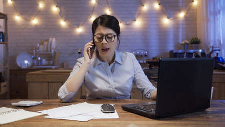 Angry female manager arguing and yelling at mobile phone while working on deadline project in evening at home.