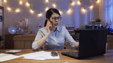 Serious woman employee frowning and talking on mobile phone while using laptop computer at home workplace in midnight
