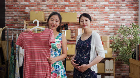 charming asian japanese female host holding casual dress face camera talking and introducing while young beautiful pregnant woman model standing beside.