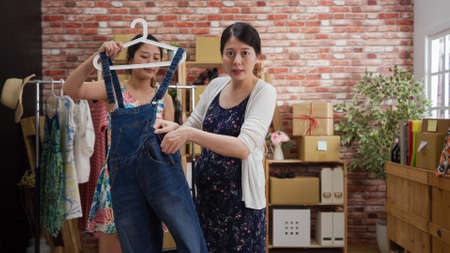 confident pregnant woman seller face camera on live streaming talking and speaking while young girl assistant helping taking denim overalls