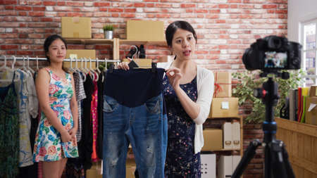 Beautiful asian chinese woman blogger sharing new collection product for maternity customer on live streaming while female staff standing in background. Stock fotó