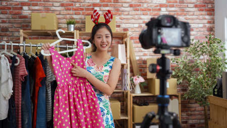 charming girl online shop owner in reindeer antler talking and looking at camera on tripod during online live streaming selling party dress. Stock fotó