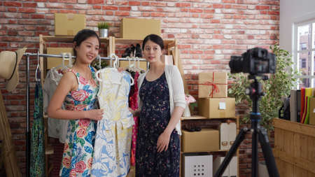 two pretty asian korean women online blogger selling colorful dress and confirm order from her customer while doing live streaming by camera on tripod.