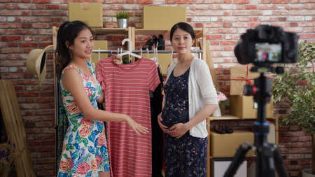 young asian chinese female trader selling product online via live streaming with camera on tripod in social media while smiling pregnant woman model wearing and presenting clothes products Stock fotó